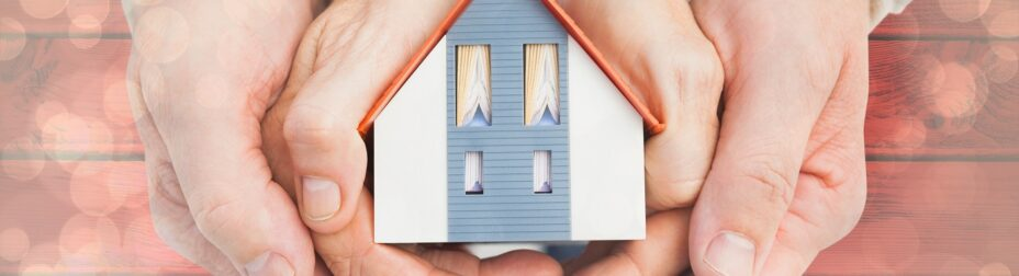 Couple holding small model house in hands against light glowing dots design pattern