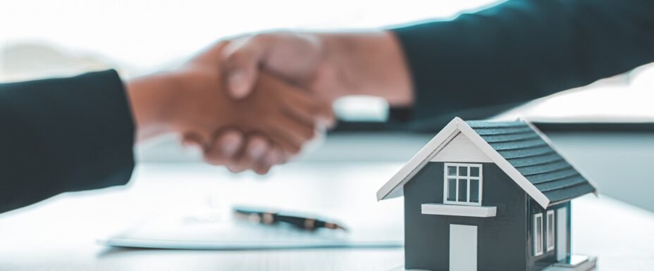 Real estate agents and customers shake hands to congratulate after signing a contract to buy a house with land and insurance